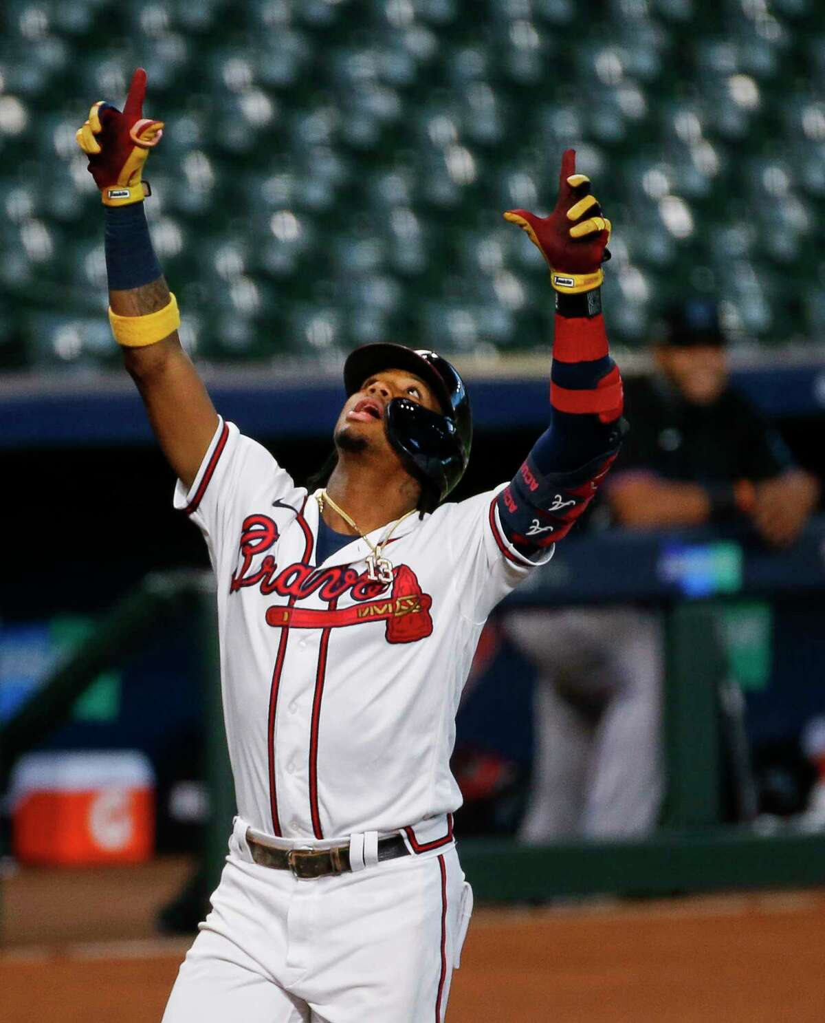 Atlanta Braves center fielder Ronald Acuña Jr. (13) celebrates after hitting a solo home run against the Miami Marlins, during the first inning in Game 1 of the National League Division Series at Minute Maid Park on Tuesday, Oct. 6, 2020, in Houston.