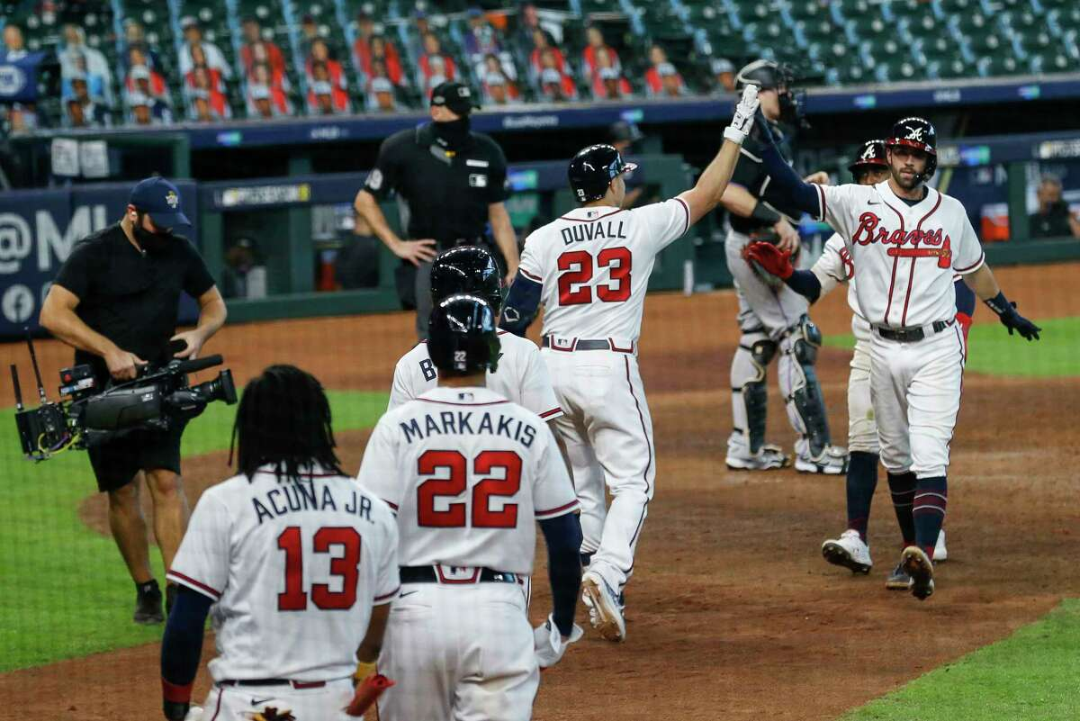 Atlanta Braves shortstop Dansby Swanson (7), right, celebrates with teammates after hitting a two-run home run against the Miami Marlins, during the seventh inning in Game 1 of the National League Division Series at Minute Maid Park on Tuesday, Oct. 6, 2020, in Houston.