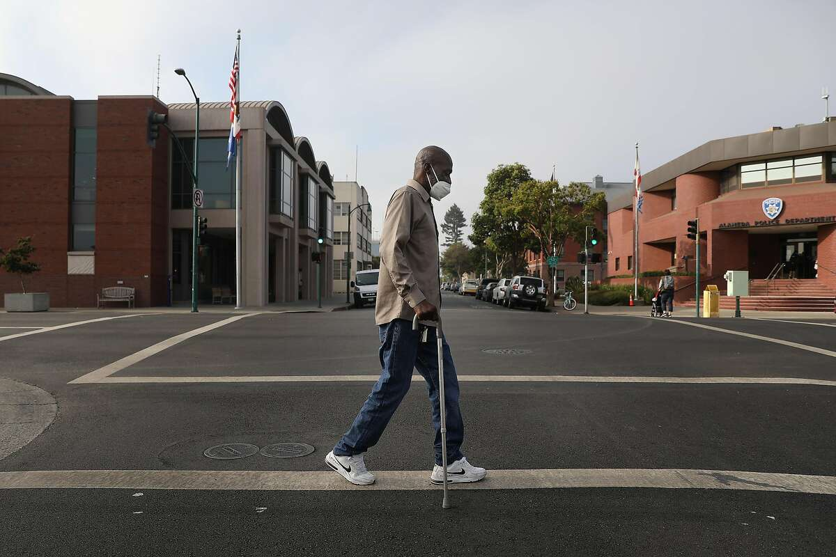 Tony Armstrong of Alameda crosses Oak Street during his daily walk through his neighborhood on Monday, October 5, 2020 in Alameda, Calif.