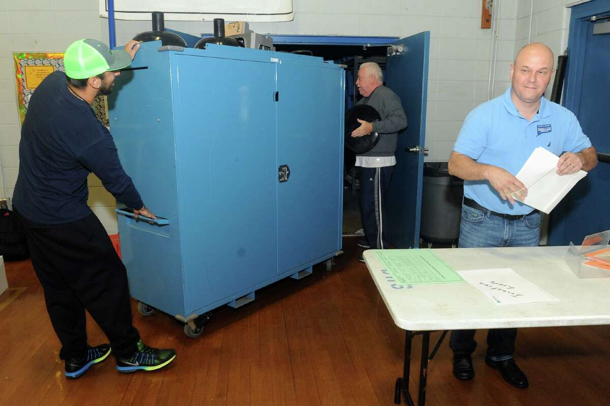 From left, Michael Gonzalez, Dave Siegler and Lou Decilio prepare to set of election polls at Bunnell High School in Stratford, Conn. Nov. 6, 2017.