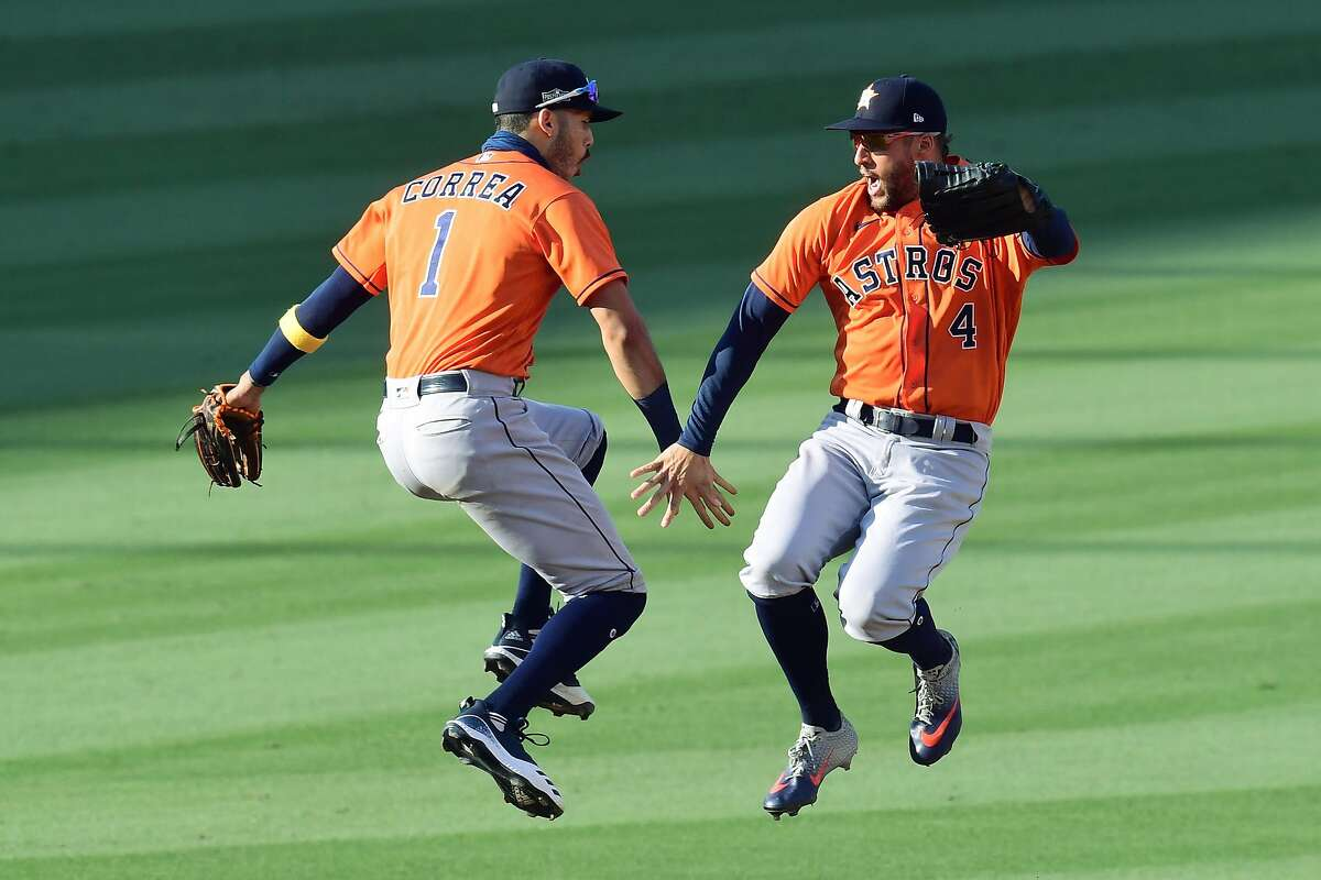 LOS ANGELES, CALIFORNIA - OCTOBER 06: George Springer #4 and Carlos Correa #1 of the Houston Astros celebrate a 5-2 win against the Oakland Athletics in Game Two of the American League Division Series at Dodger Stadium on October 06, 2020 in Los Angeles, California. (Photo by Harry How/Getty Images)
