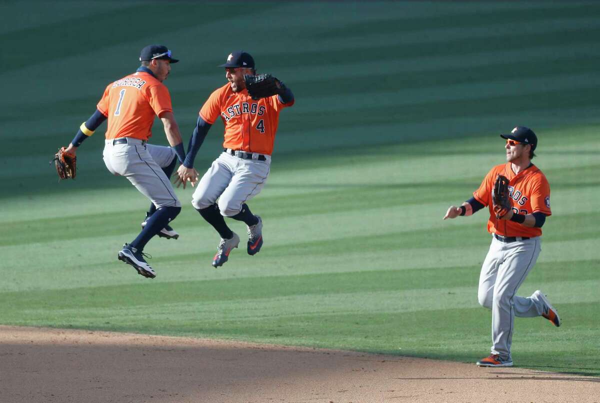 Houston Astros Carlos Correa (1) jumps up with George Springer (4) and Josh Reddick (22) as they celebrated the Astros 5-2 win over the Oakland Athletics after Game 2 of the American League Division Series, at Dodger Stadium, Tuesday, October 6, 2020, in Los Angeles.