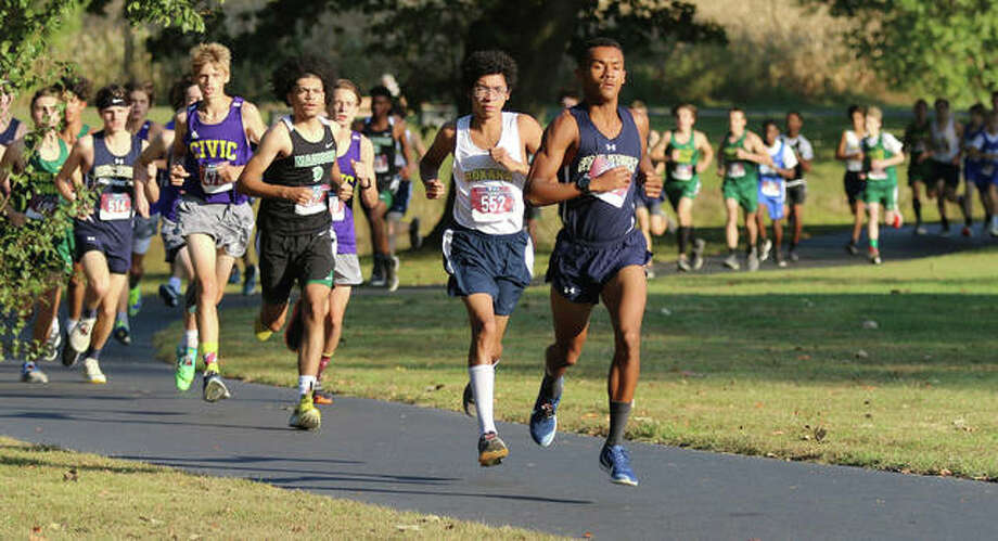 Father McGivney's Tyler Guthrie (right) and Roxana's Carlos Ruvalcaba run 1-2 while leading the pack in the opening quarter-mile of the Madison County Small-Schools Meet on Tuesday at Belk Park in Wood River. Guthrie won the three-mile cross country race in a personal-best time 14 minutes, 53.80 seconds. Photo: Greg Shashack / The Telegraph