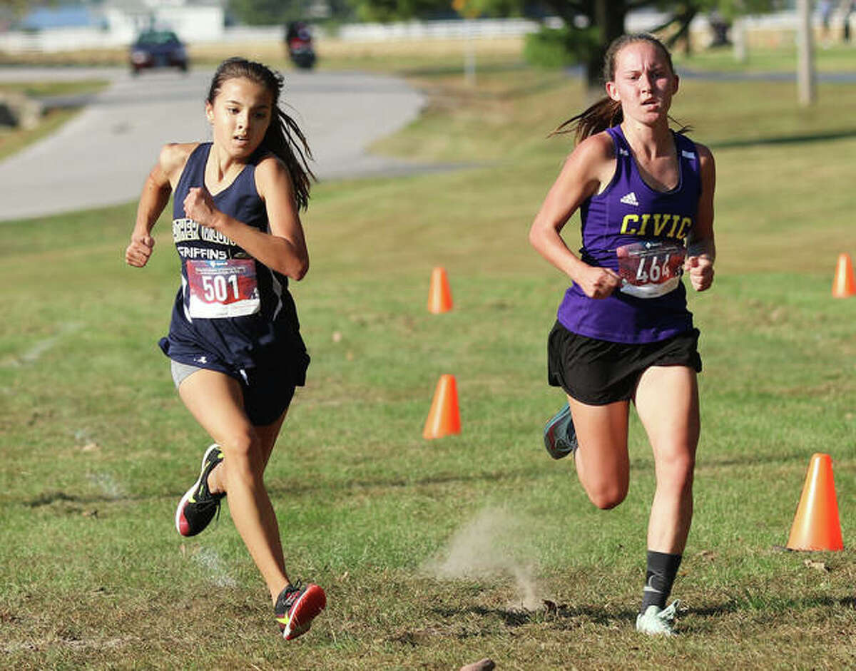 CM sophomore Hannah Meiser and Father McGivney freshman Kaitlyn Hatley sprint toward the finish in the Madison County Small-Schools Meet on Tuesday at Belk Park in Wood River. Meiser won in 19:03.50, with Hatley second in 19:03.60.