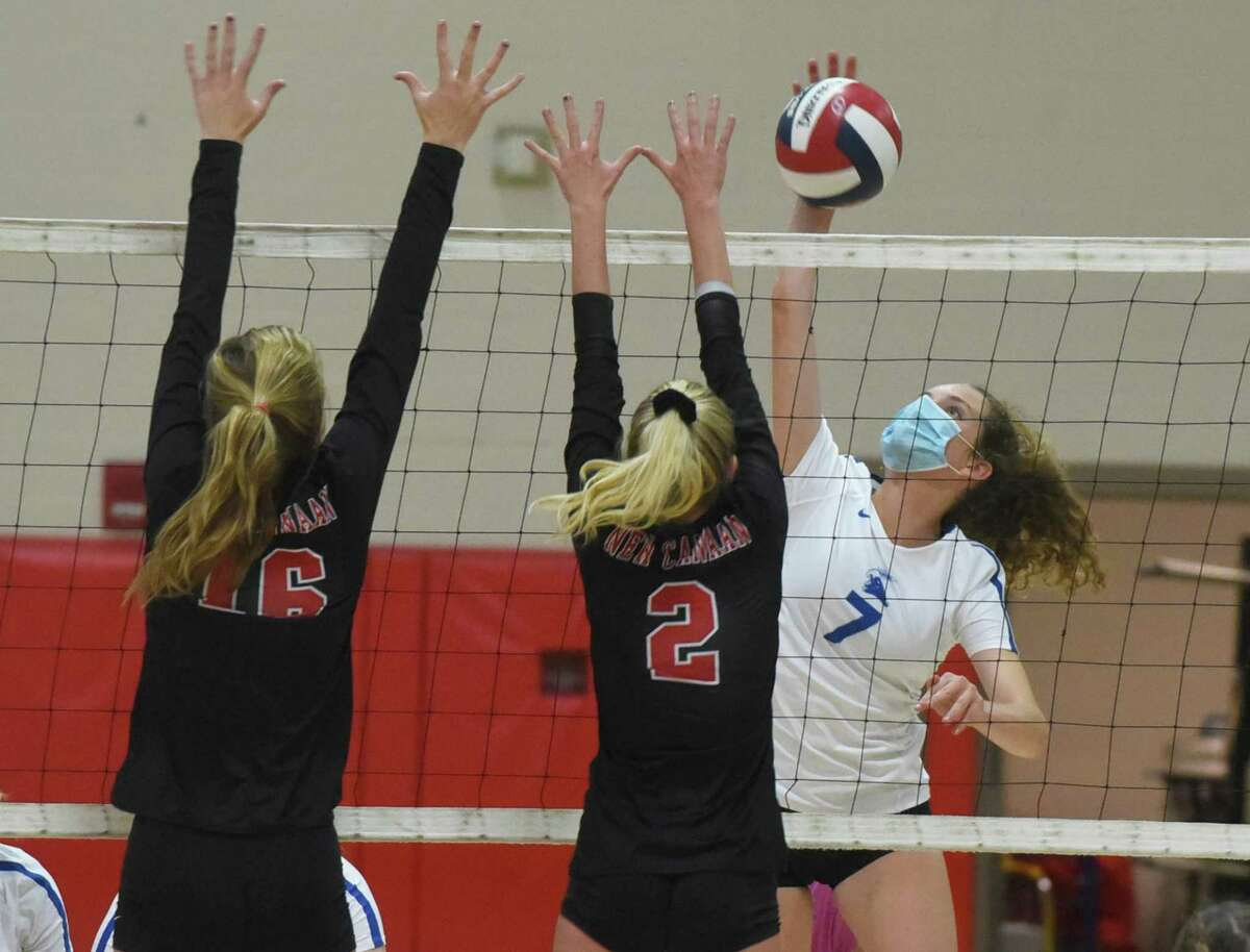 Darien's Jillian Roche (7) takes a shot as New Canaan's Elle Sneddon (2) and Diane Wallace (16) attempt a block during Tuesday's game.