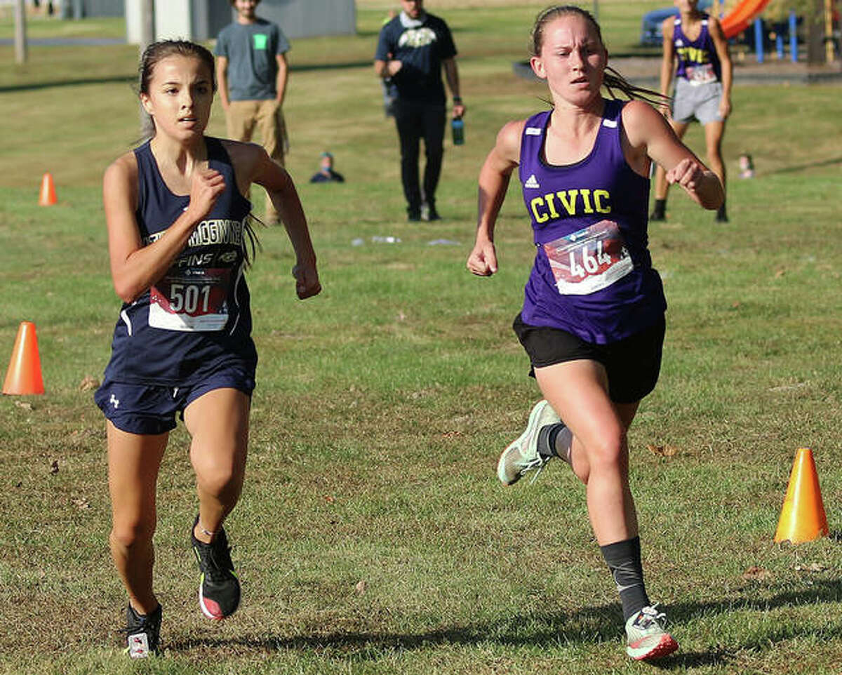 Father McGivney's Kaitlyn Hatley, left, and Civic Memorial's Hannah Meiser sprint to the finish line at the Madison County Meet on Tuesday in Belk Park in Wood River.