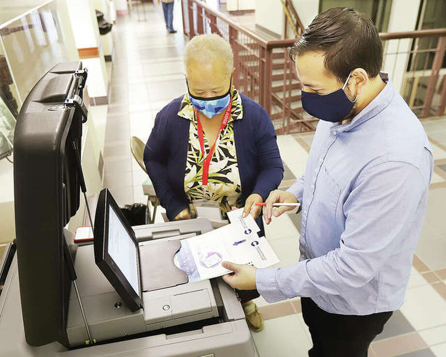 Election Judge Penny Alexander, center, helps a man place his ballot into the tabulation machine Friday at the Madison County Administration Building in Edwardsville on the second day of early voting in Madison County. Turnout has apparently been steady with voters wearing masks and practicing social distancing. Early in-person voting will continue at the administration building weekdays 8:30 a.m. to 4:30 p.m. For more information on early in-person voting, see the story inside today's issue. Photo: John Badman | Hearst Newspapers