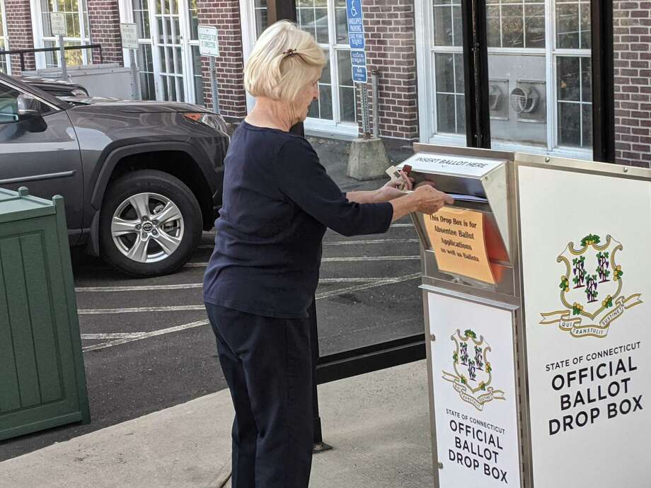 Greenwich resident Birgitta Longnecker drops off her absentee ballot at Town Hall on Tuesday morning. Town residents have been requesting ballots in record numbers this year and there are drop off locations at Town Hall and the lobby of the police station. Photo: Ken Borsuk / Hearst Connecticut Media /