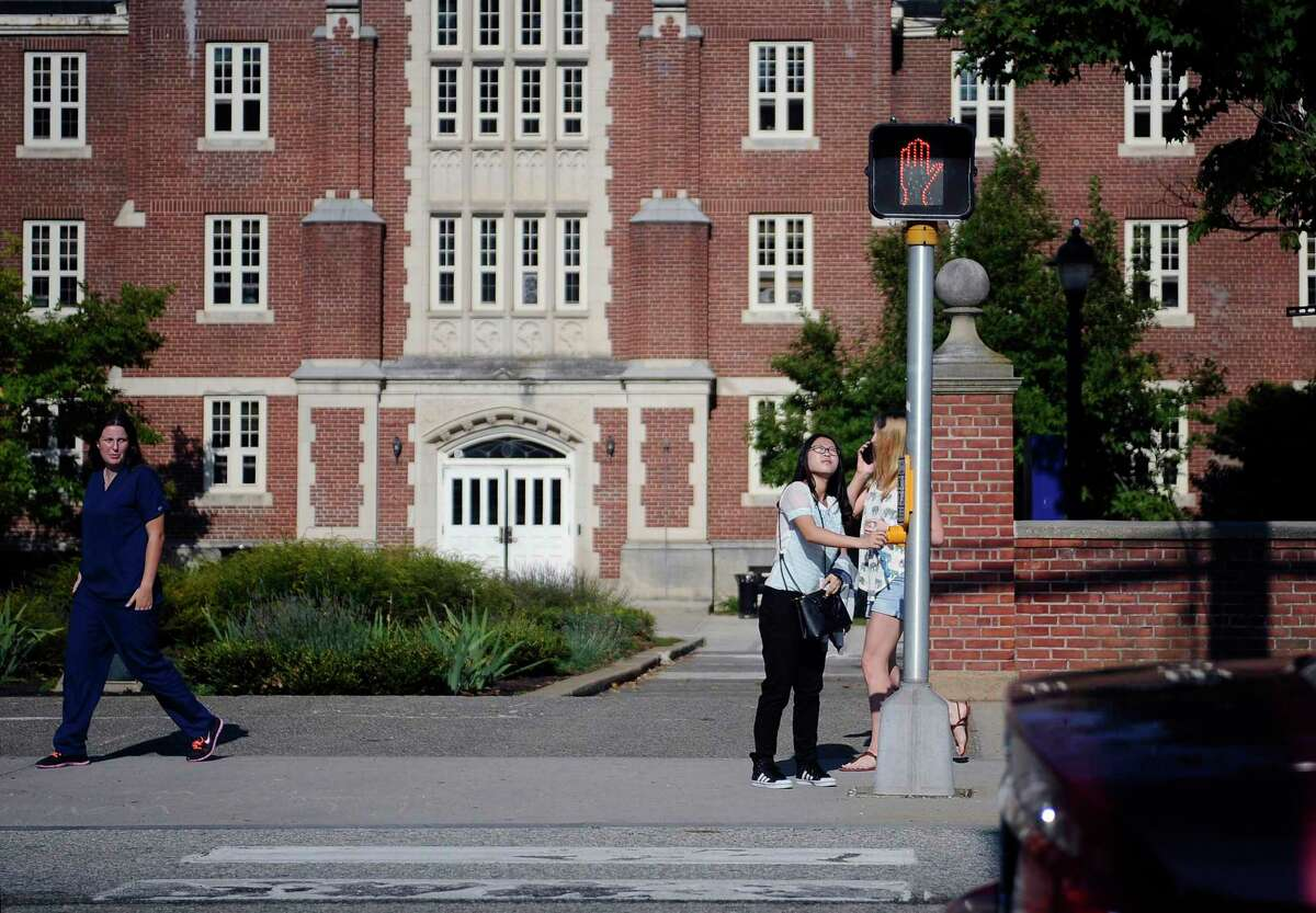 FILE- In this Sept. 18, 2015 file photo, a University of Connecticut student waits for the traffic light to change outside of a dormitory building on the University of Connecticut campus in Storrs, Conn. (AP Photo/Jessica Hill, File)