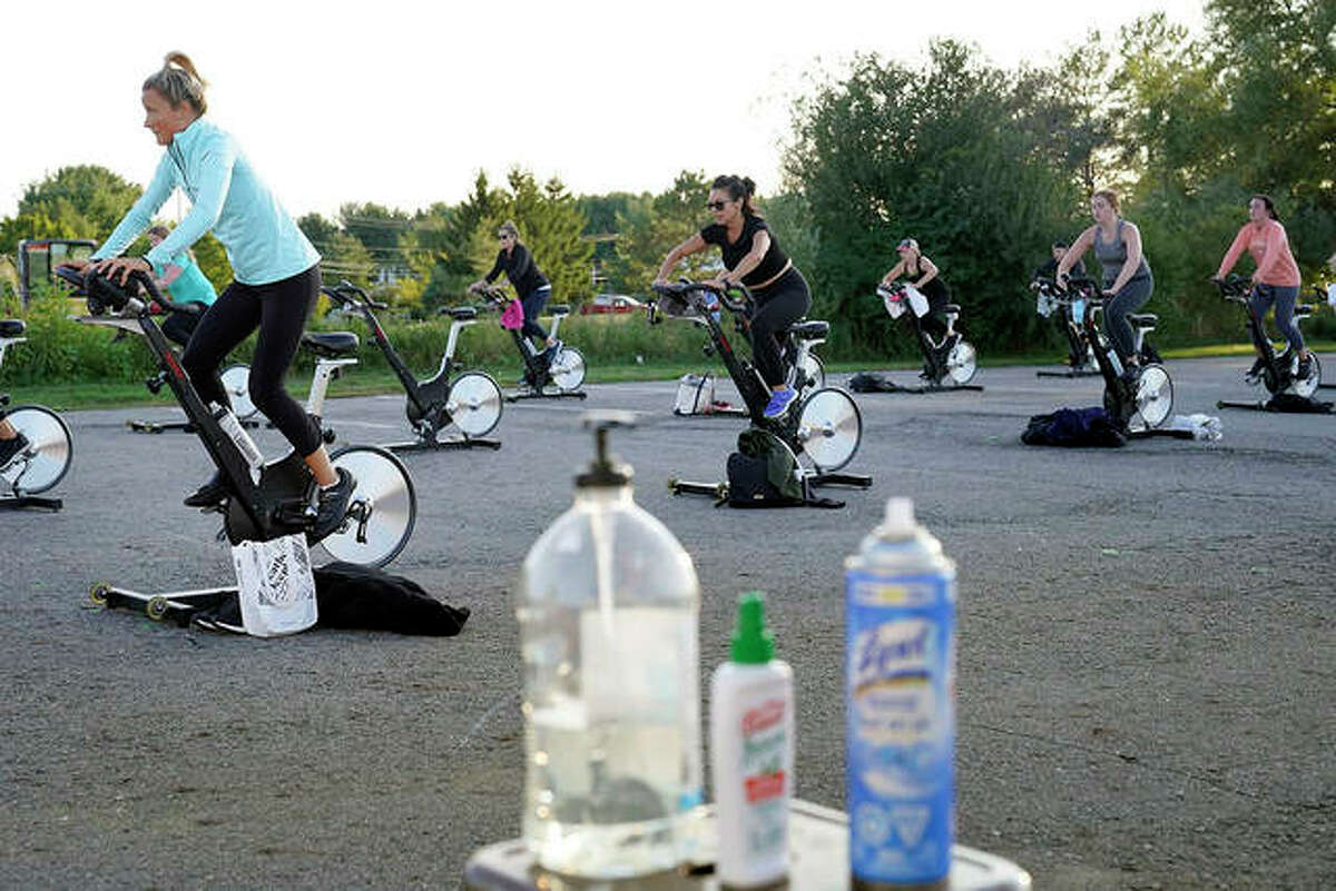 Jackie Brennan pedals with others on stationary exercise bikes during a spinning class in a parking lot outside Fuel Training Studio. The gym's revenue is down about 60% during the COVID-19 pandemic.