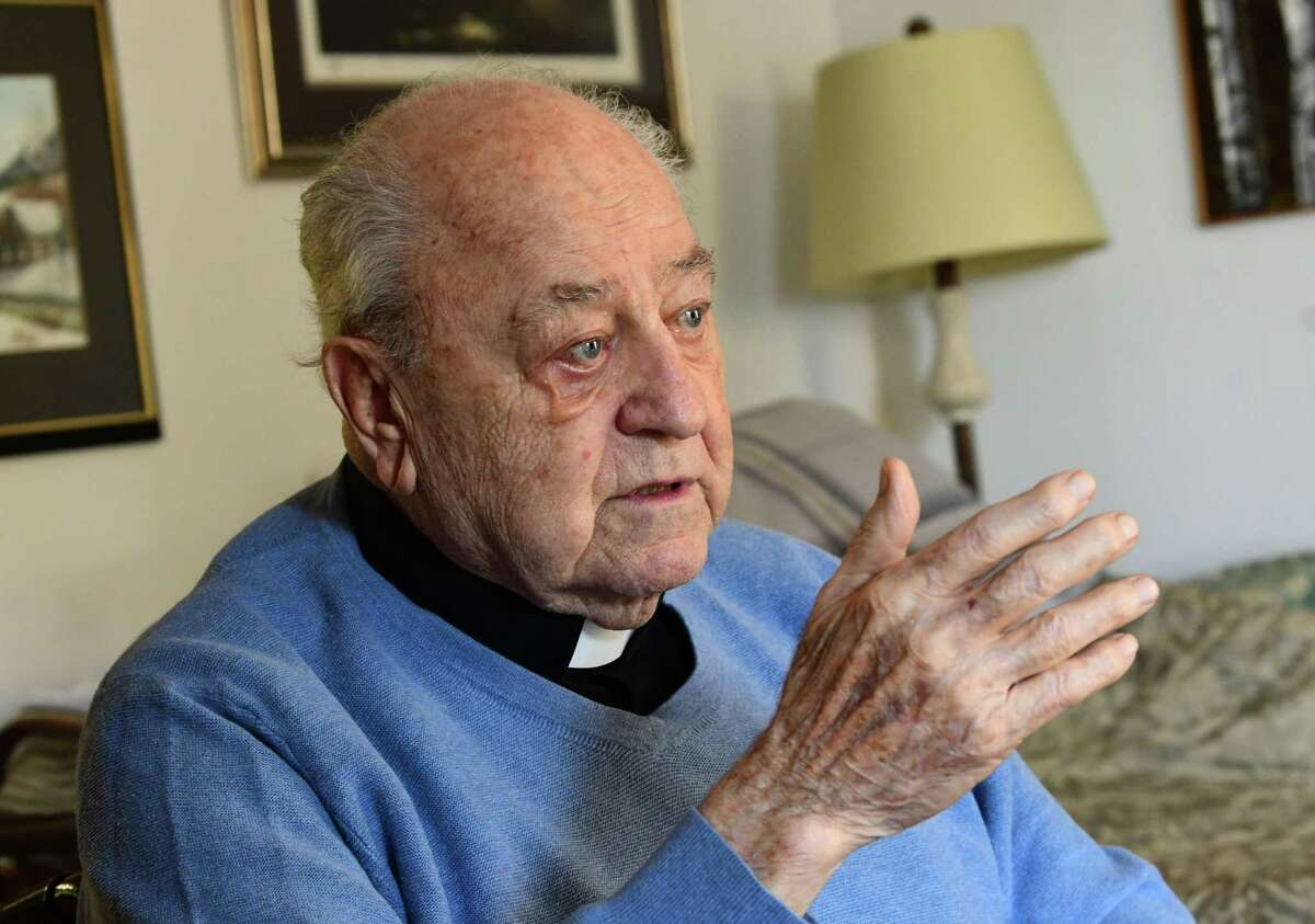 Father Peter Young, 90, talks with a visitor at his home on Tuesday, Oct. 6, 2020 in Albany, N.Y. (Lori Van Buren/Times Union)