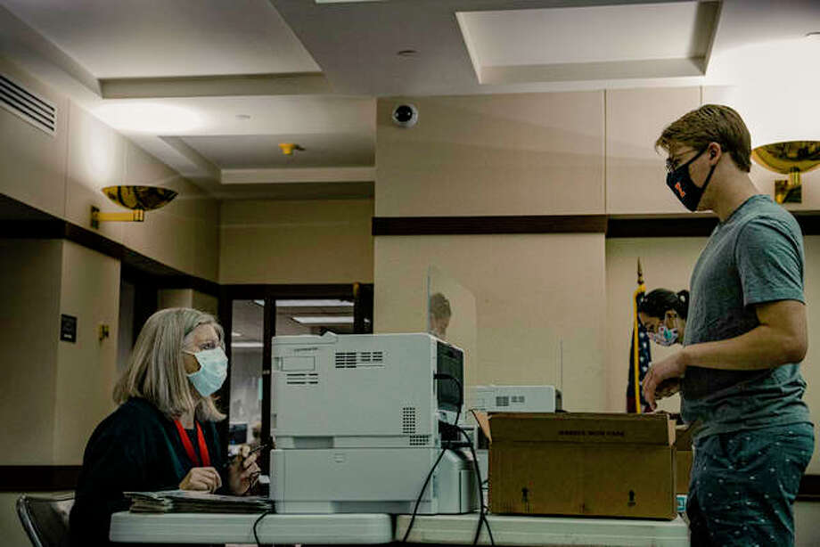 Election judge Sue Betts works to get a ballot to a Madison County resident during an early voting day on Tuesday in the Madison County Administration Building in Edwardsville. Photo: Tyler Pletsch | The Intelligencer