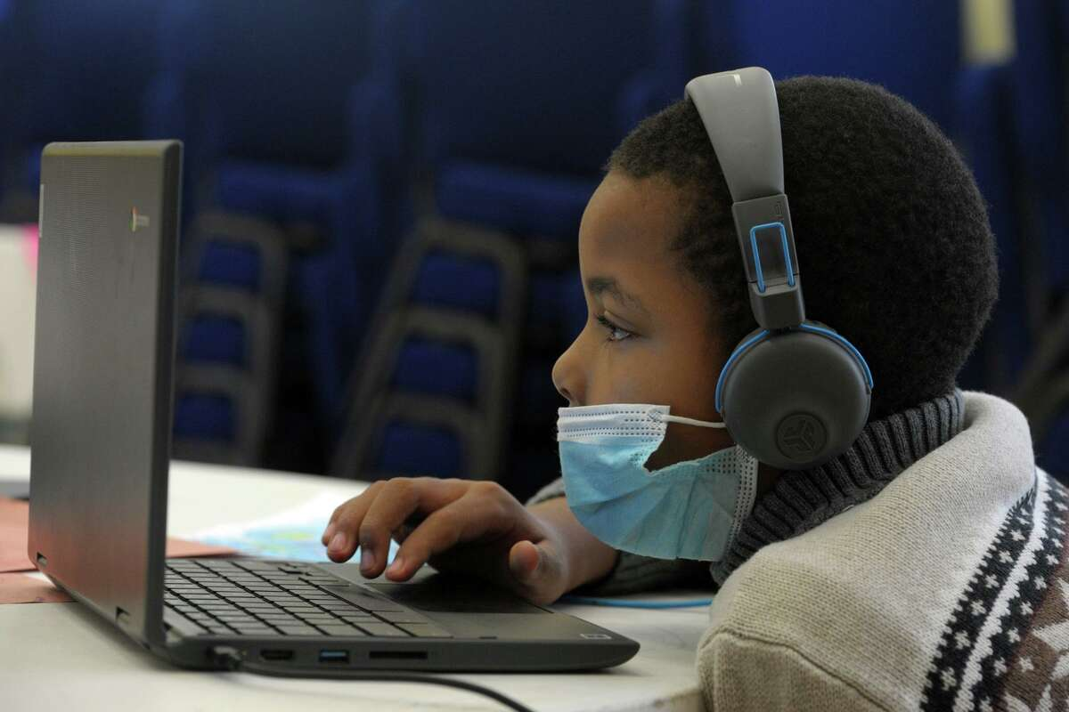 Fourth grader Jaylen Carver works on a laptop computer at the community learning hub at First Cavalry Baptist Church, in New Haven, Conn. Oct. 6, 2020.