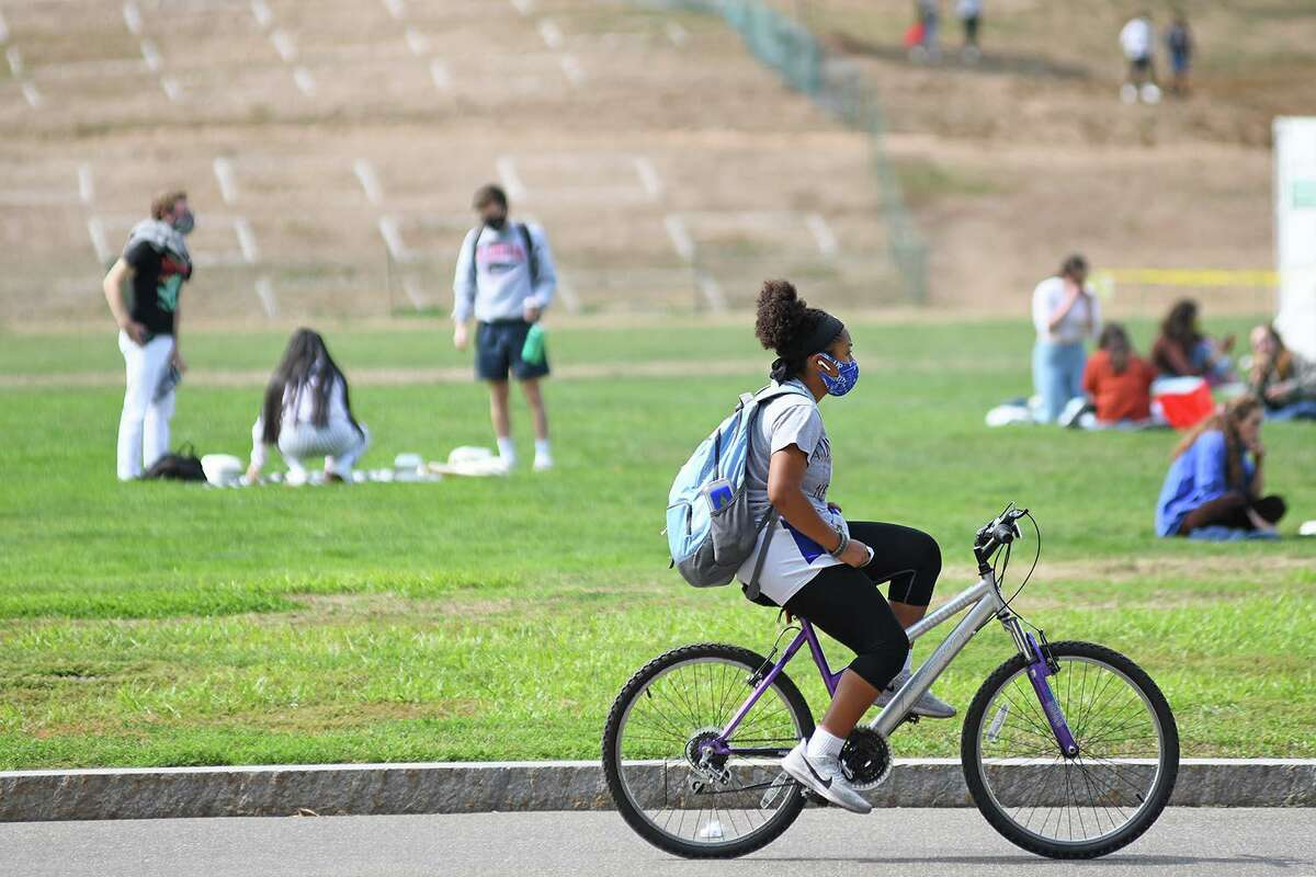 A Wesleyan University students cycles around campus in Middletown wearing a face mask.