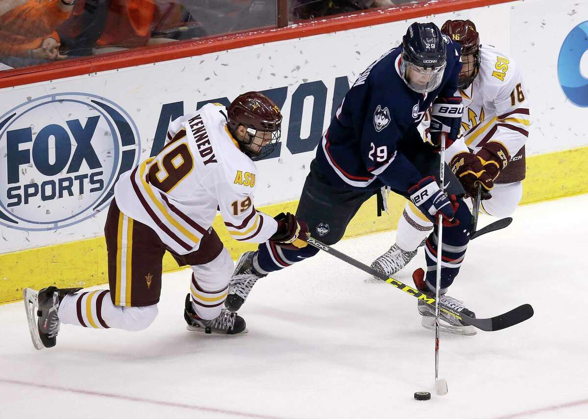 UConn's Tage Thompson (29) battles for the puck with Arizona State forward Matt Kennedy and forward Ryan Belonger (16) during the first period of an NCAA college game at the Desert Hockey Classic tournament, Sunday, Jan. 10, 2016 in Glendale, Ariz