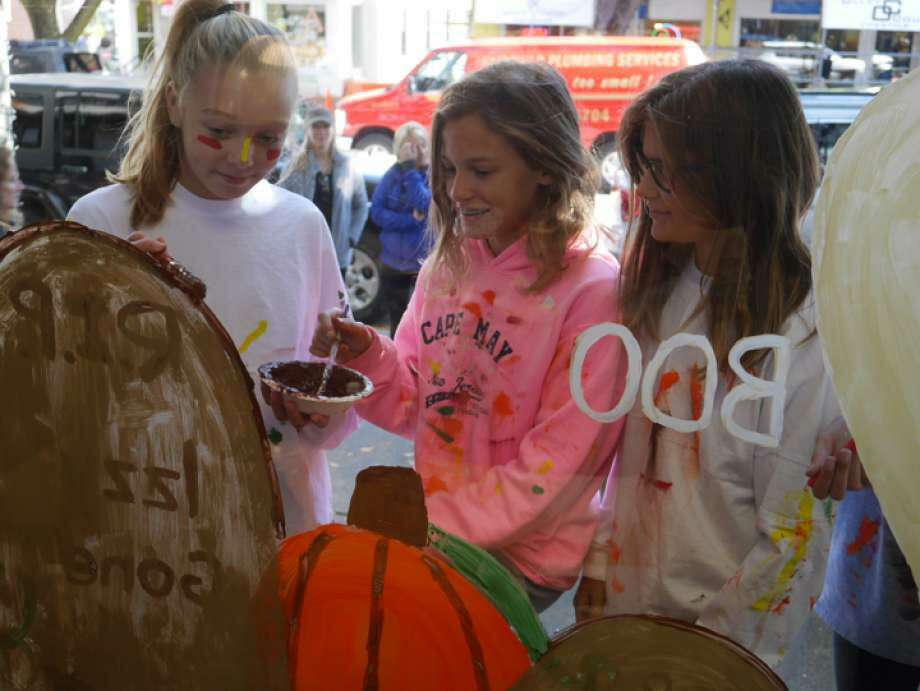 Kids paint windows at a past Halloween Window Painting event hosted by Ridgefield Parks & Recreation. Photo: Contributed Photo