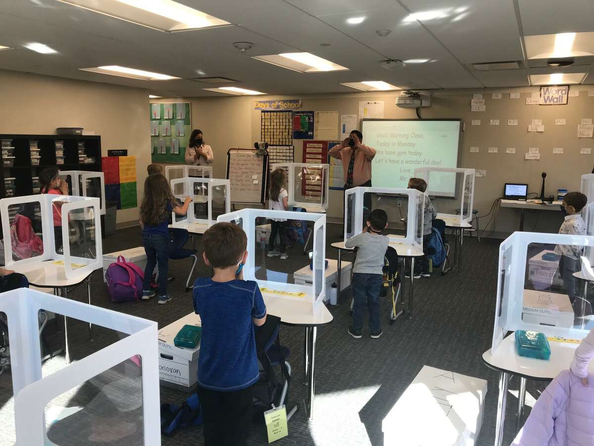 Kindergarten students in Sal Giaimo's class stand at their desks outfitted with sneeze guards. Full kindergarten and first-grade classes returned to Miller-Driscoll School on Monday, Oct. 5.