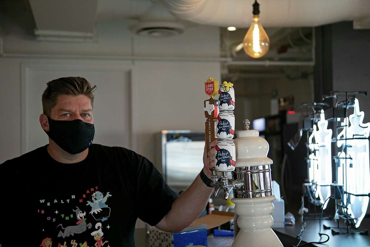 Matt Bruhn, general manager of Pabst Brewing Co., holds a tap behind the bar at the company's new headquarters in downtown San Antonio.