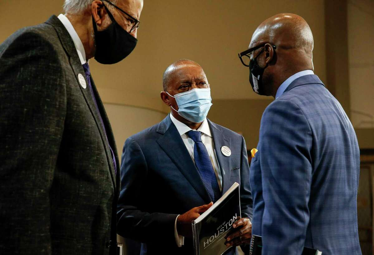 Houston Mayor Sylvester Turner, center, speaks with Chairman Larry Payne, left, and Bishop James Dixon, right, after a press conference to announce the recommendations of the Mayor's Task Force on Policing Reform on Wednesday, Sept. 30 2020, at city hall in Houston.