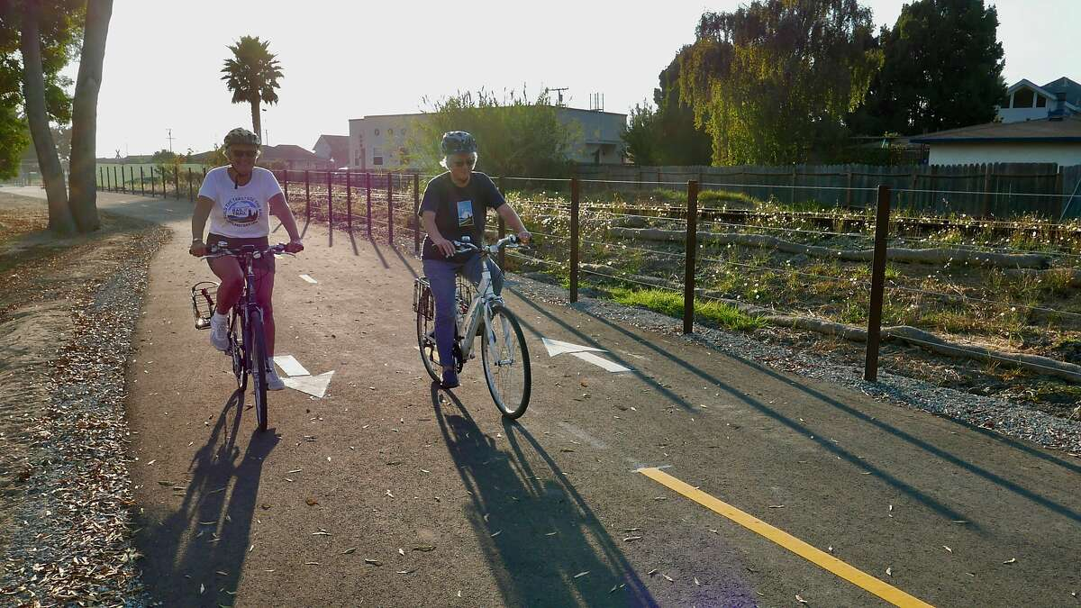 A pair of bicyclists enjoy the Coastal Rail Trail in Santa Cruz, where construction is underway to extend the trail.