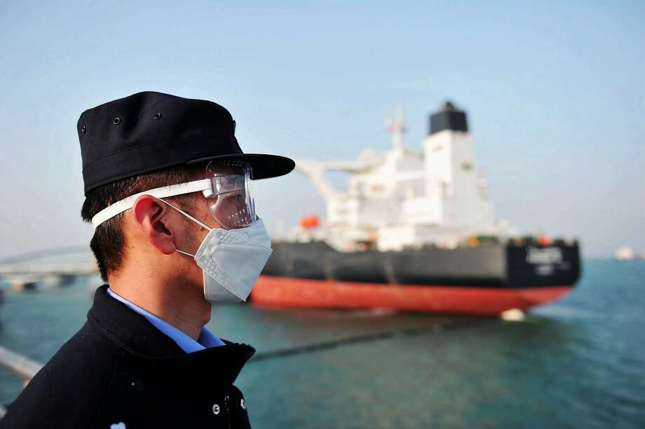 This photo taken on March 20, 2020 shows a police officer wearing a mask amid concerns over the COVID-19 coronavirus while keeping watch as a Kuwaiti oil tanker unloads crude oil at the port in Qingdao, in China's eastern Shandong province. (Photo by STR / AFP) / China OUT (Photo by STR/AFP via Getty Images) Photo: Str, AFP Via Getty Images