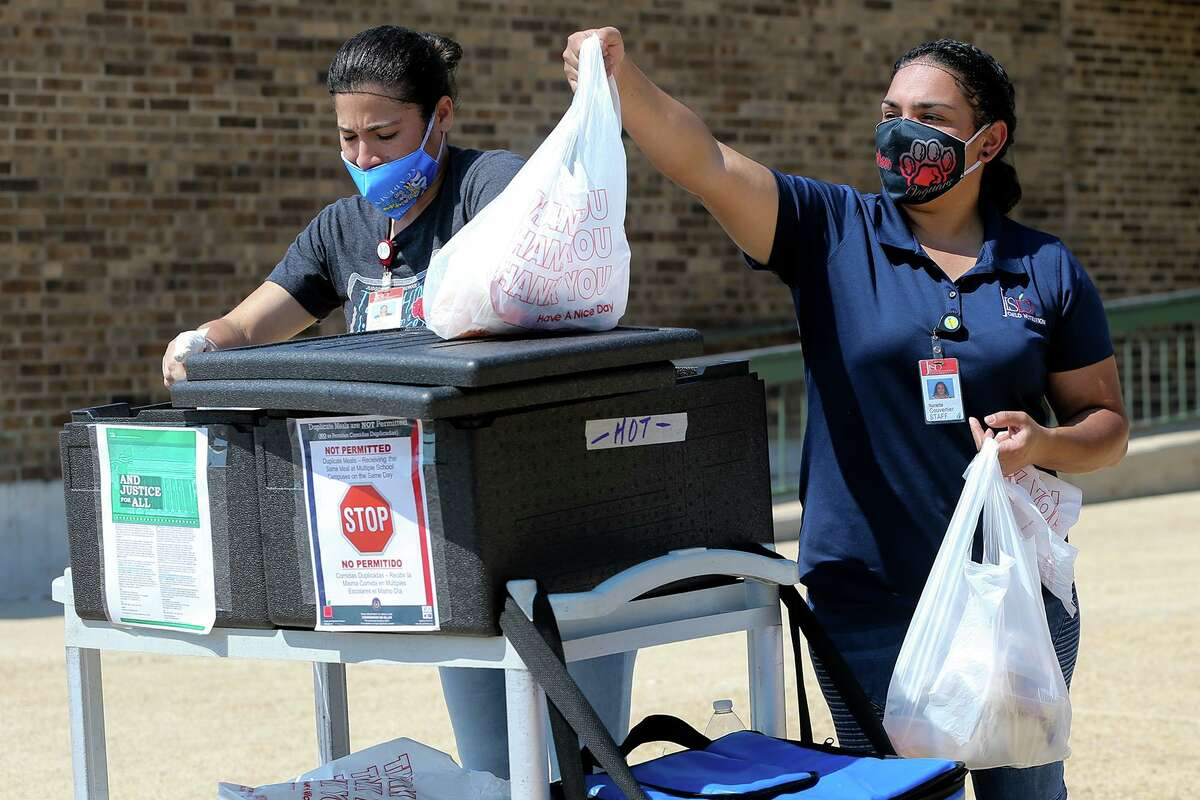 Yaritza Olivarado, left, and Nanette Couvertier with the Judson ISD Child Nutrition Department distribute free breakfasts and lunches for students in the school district at Judson Middle School on Oct. 2.
