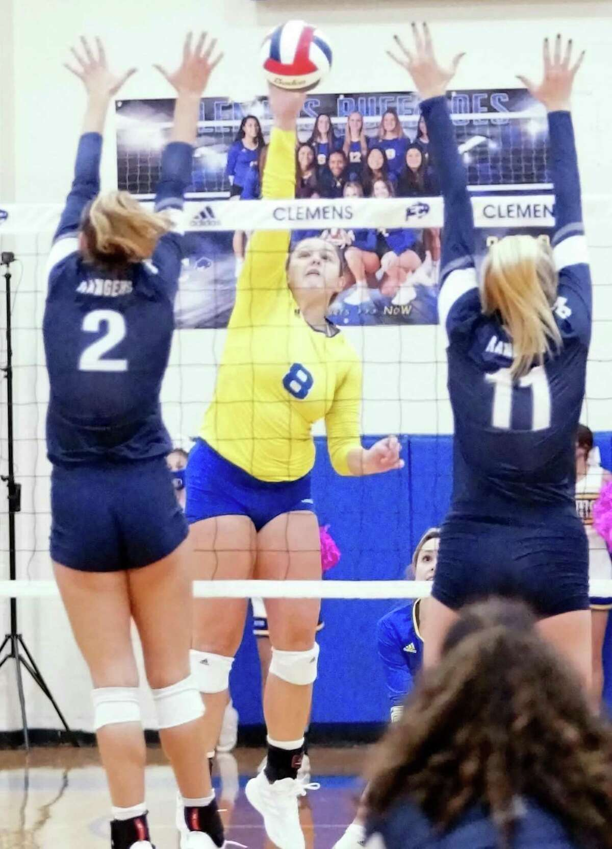 Clemens' Canada Buchanan (8) tries to slice a kill between Smithson Valley's Bekah Williams (2) and Alexa Pyle (11) Friday. Clemens fell to the visiting Rangers 3-1 on Friday .