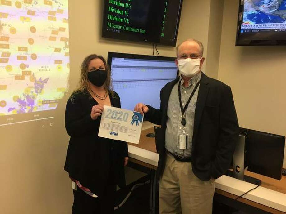 """Heather Lowrey, emergency response specialist, and Larry Magelitz, manager, Crisis Management, display the """"Ambassador or Excellence"""" award Ameren Illinois received from the National Weather Service."""