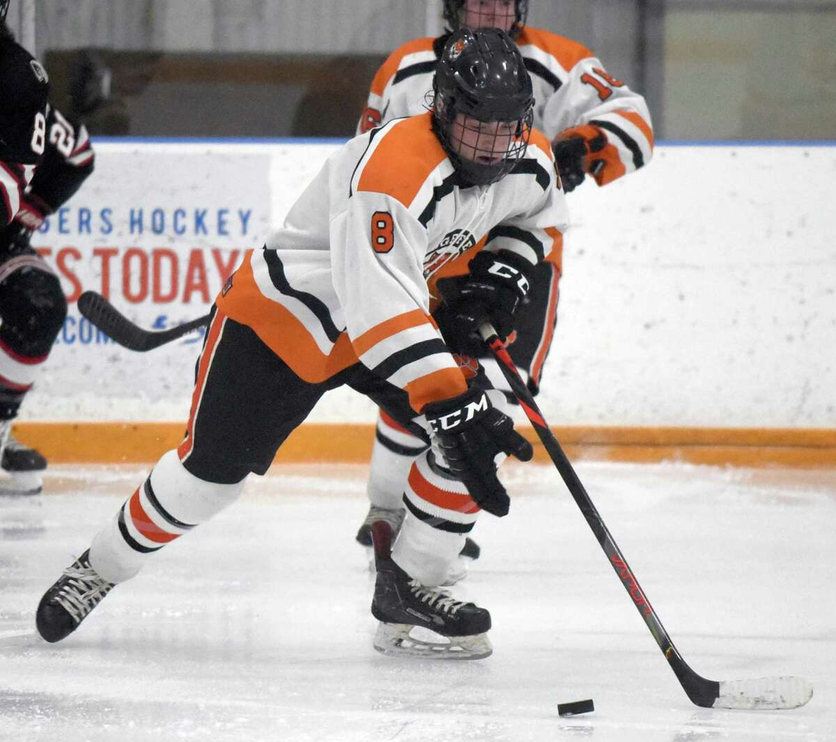 Ridgefield's Kees van Wees (8) skates with the puck during a boys ice hockey game between New Canaan and Ridgefield at the Winter Garden.