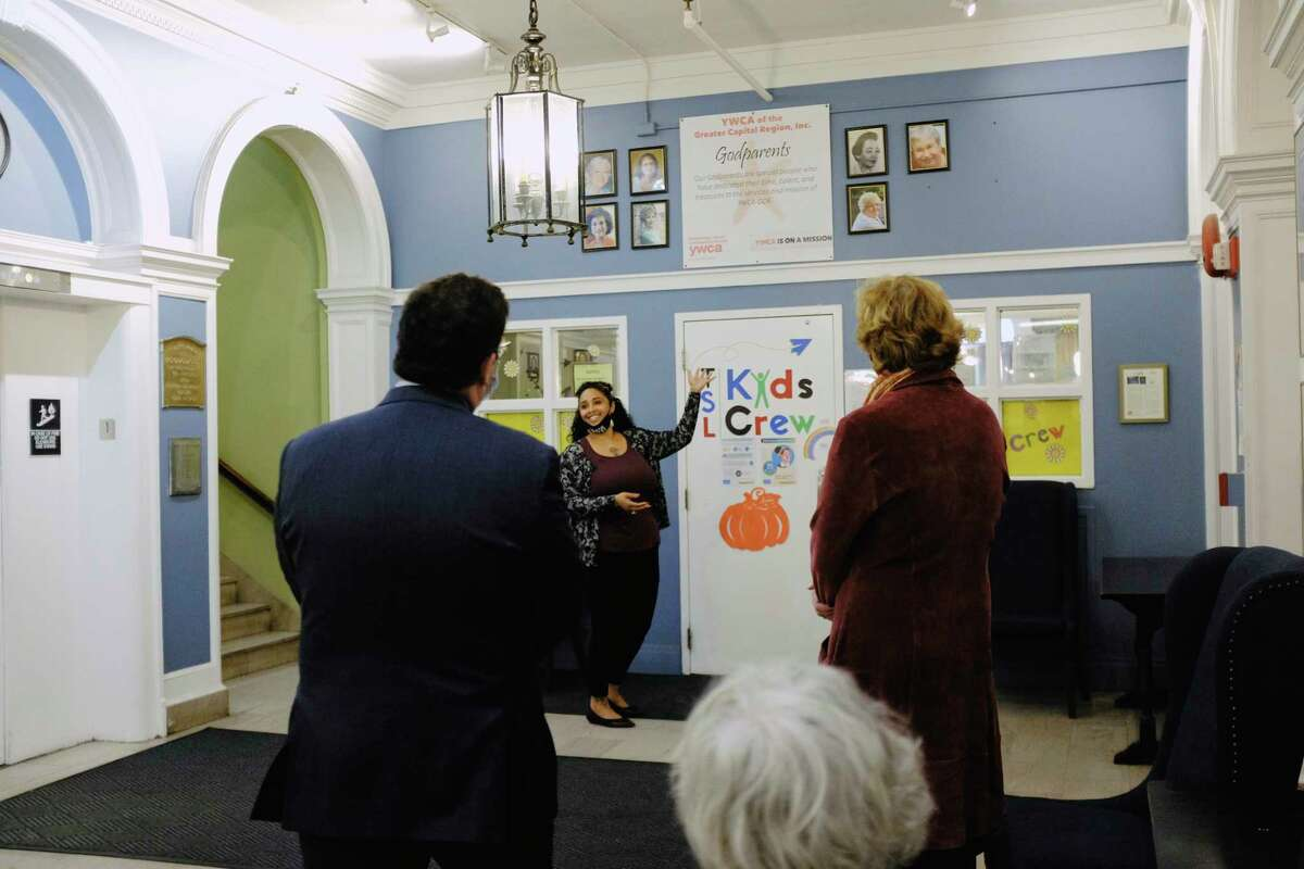 Starletta Smith, executive director of the YWCA of the Greater Capital Region, shows off the newly installed area that honors the organization's Godparents on Wednesday, Oct. 7, 2020, in Troy, N.Y. The YWCA-GCR inducted two Godmothers on Wednesday, Judge Beth Walsh, and Sherry Rounds, a former executive director of the YWCA-GCR. The organization's Godparents are those who have given their time, talents,a nd treasures to the organization. The YWCA-GCR was founded in 1883. (Paul Buckowski/Times Union)