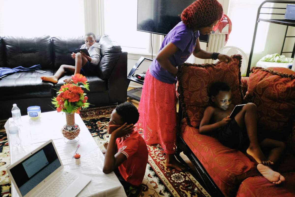 Bisoci Mnyomoelwa, second from right, a senior at Albany High School, sets her brother, Asukulu Oredi, up on the couch for his remote classroom time at their home on Monday, Oct. 5, 2020, in Albany, N.Y. Bisoci's other brothers, Mmungar Oredi, background, and Mlondani Mnyomoelwa try to get through their remote learning at the same time. (Paul Buckowski/Times Union)