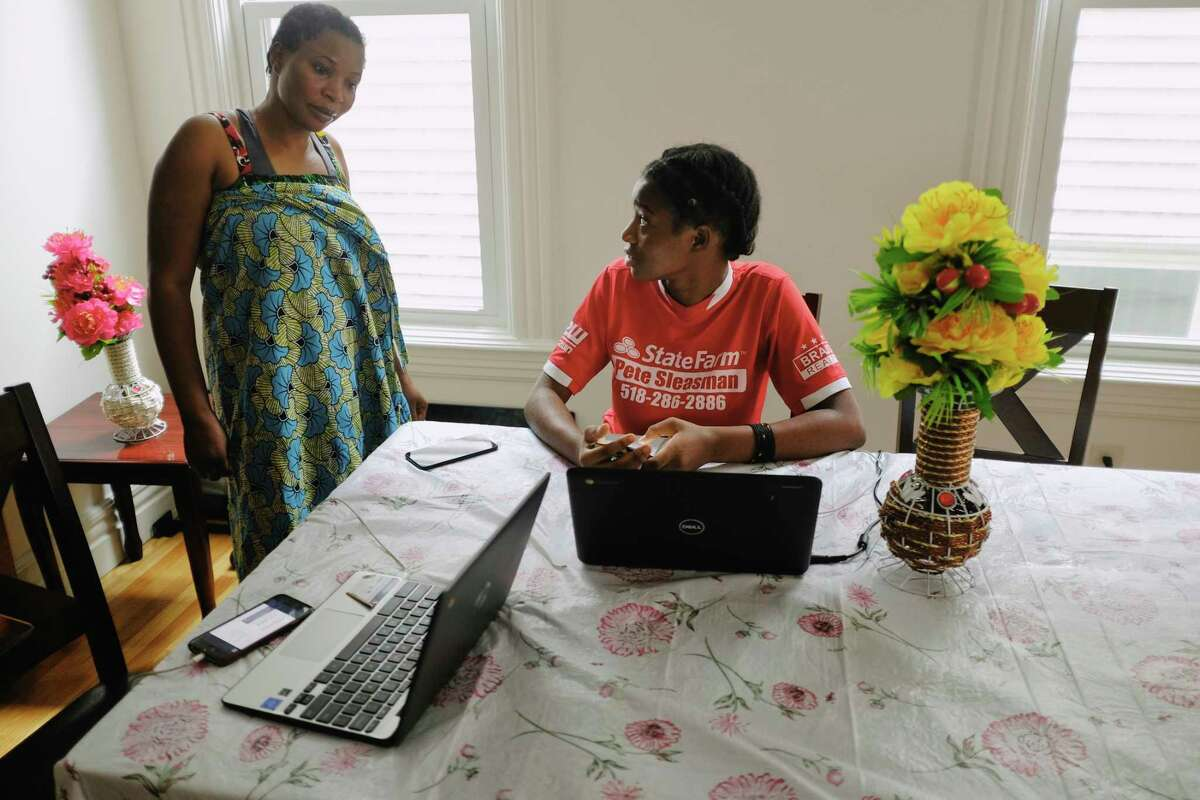 Sifa Eca, left, talks with her daughter, Ungwa Mnyomoelwa, a sophomore at Albany High School, as she works on her remote learning at their home on Monday, Oct. 5, 2020, in Albany, N.Y. (Paul Buckowski/Times Union)