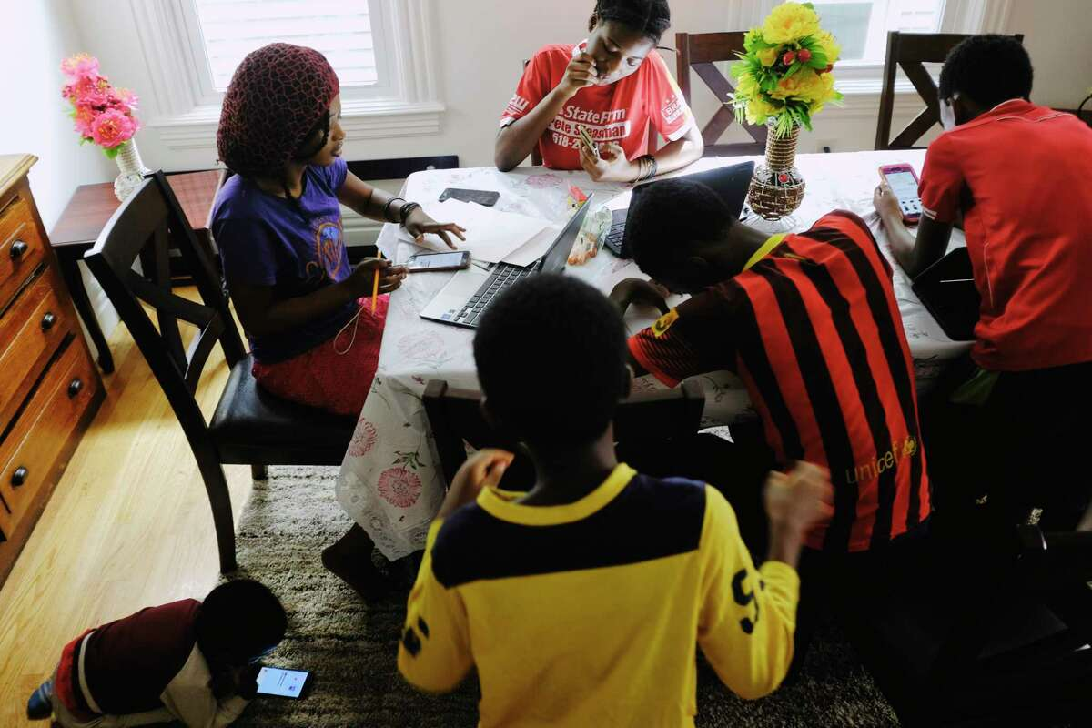 Siblings, Bisoci Mnyomoelwa, Ungwa Mnyomoelwa, Ababele Mnyomoelwa, Mlondani Mnyomoelwa, Bahelanya Mnyomoelwa, and Ali Oredi work on their remote learning at their home on Monday, Oct. 5, 2020, in Albany, N.Y. (Paul Buckowski/Times Union)