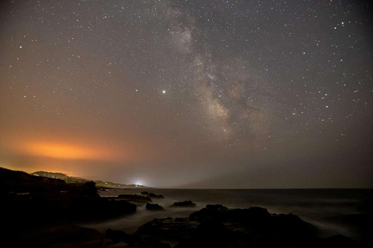 Stars above Half Moon Bay are visible even as wildfires illuminate the sky in August.
