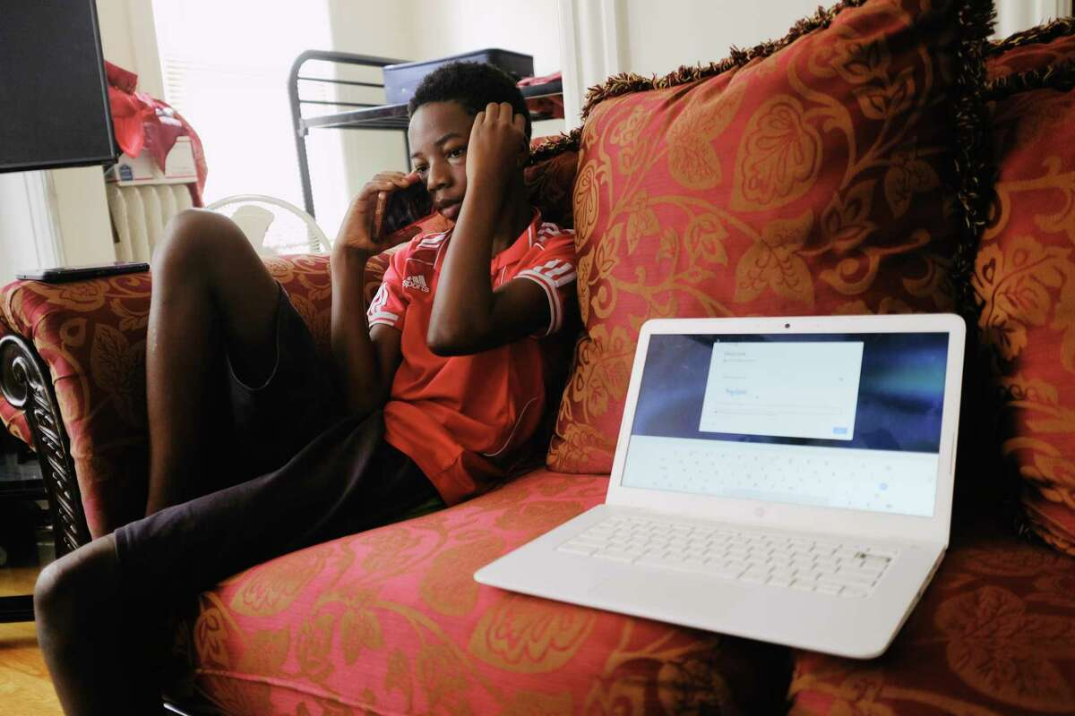 Paul Buckowski's images of a refugee family grappling with the challenges of distance learning were honored by the state News Publishers Association. Above: Mlondani Mnyomoelwa, a seventh grader in the Albany School district, waits on hold for help on resetting his password to be able to sign in to his Chromebook.