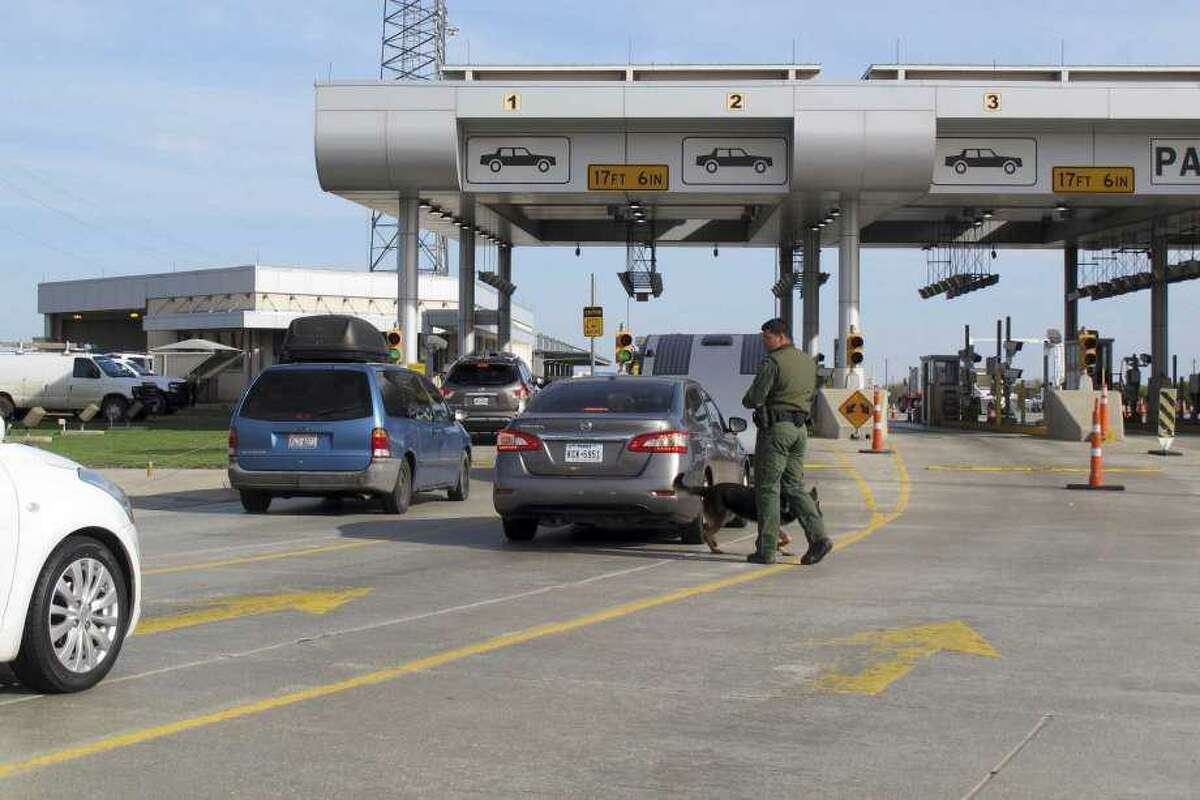 Inspectors and dogs walk around the cars at the Interstate 35 checkpoint near Laredo.