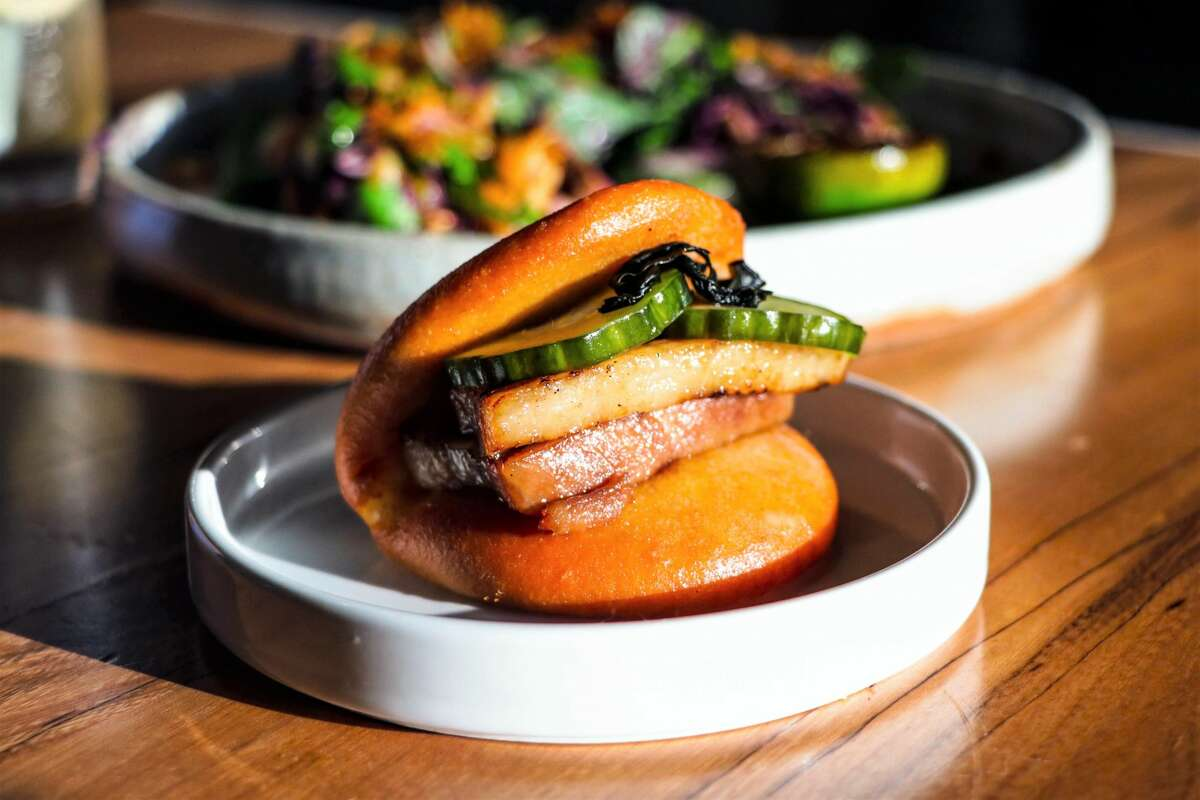 Starters include a pork belly bao with caramelized fish sauce, beef tallow aioli, and pickled cucumber.