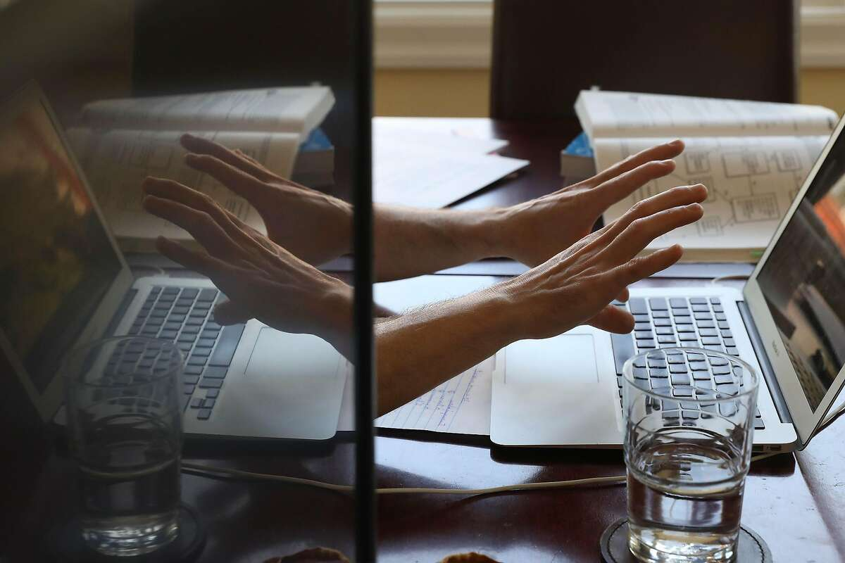 Daniel Schweitzer, state bar tutor, gestures with his hands as he works on a lap top while talking to a client during a tutoring session from his home on Wednesday, September 16, 2020 in San Francisco, Calif.