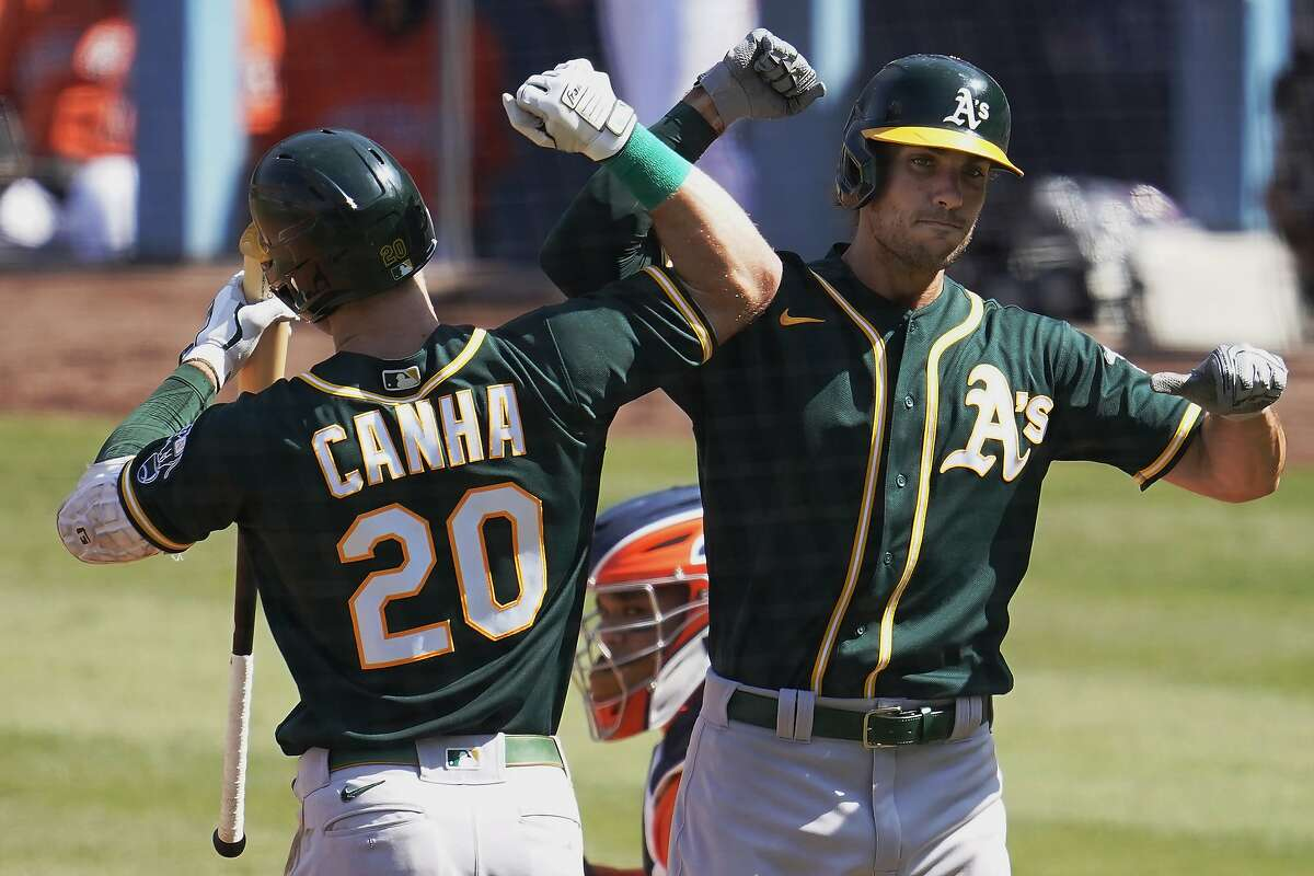 Oakland Athletics' Matt Olson, right, is congratulated by Mark Canha after hitting a solo home run against the Houston Astros during the fourth inning of Game 3 of a baseball American League Division Series in Los Angeles, Wednesday, Oct. 7, 2020.
