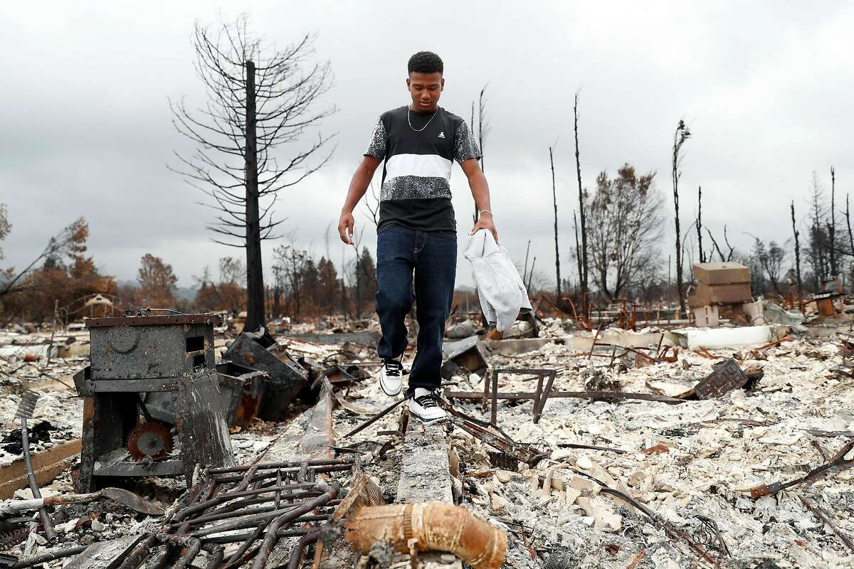 Cardinal Newman football player Nikko Kitchen looks to salvage items on Friday, November 3, 2017, while visiting his family's house that burned to the ground during the Tubbs' Fire in the Coffey Park subdivision in Santa Rosa, Calif..