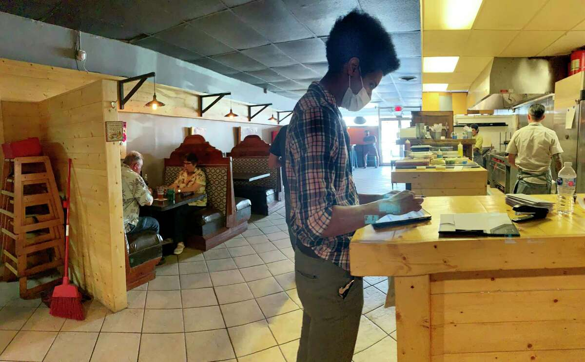Jonathan Valera processes a customer's order at SoHill Cafe on May 1.