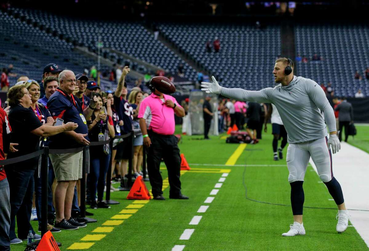 Texans defensive end J.J. Watt, right, tosses a football to a fan before an October 2019 game at NRG Stadium.