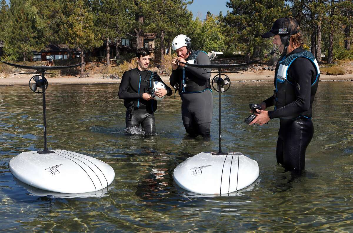 Students Kevin Burrage (left) and Connor Bugbee (center) with instructor Matt Cook during an efoil class lesson on Lake Tahoe at Kings Beach.