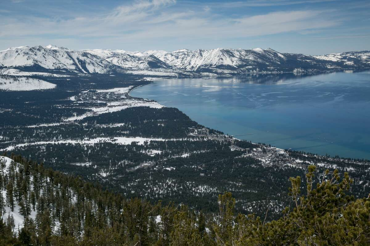 The lake and snow-covered mountains are viewed from the Heavenly Ski Resort observation deck on March 17, 2019, in South Lake Tahoe, Calif.