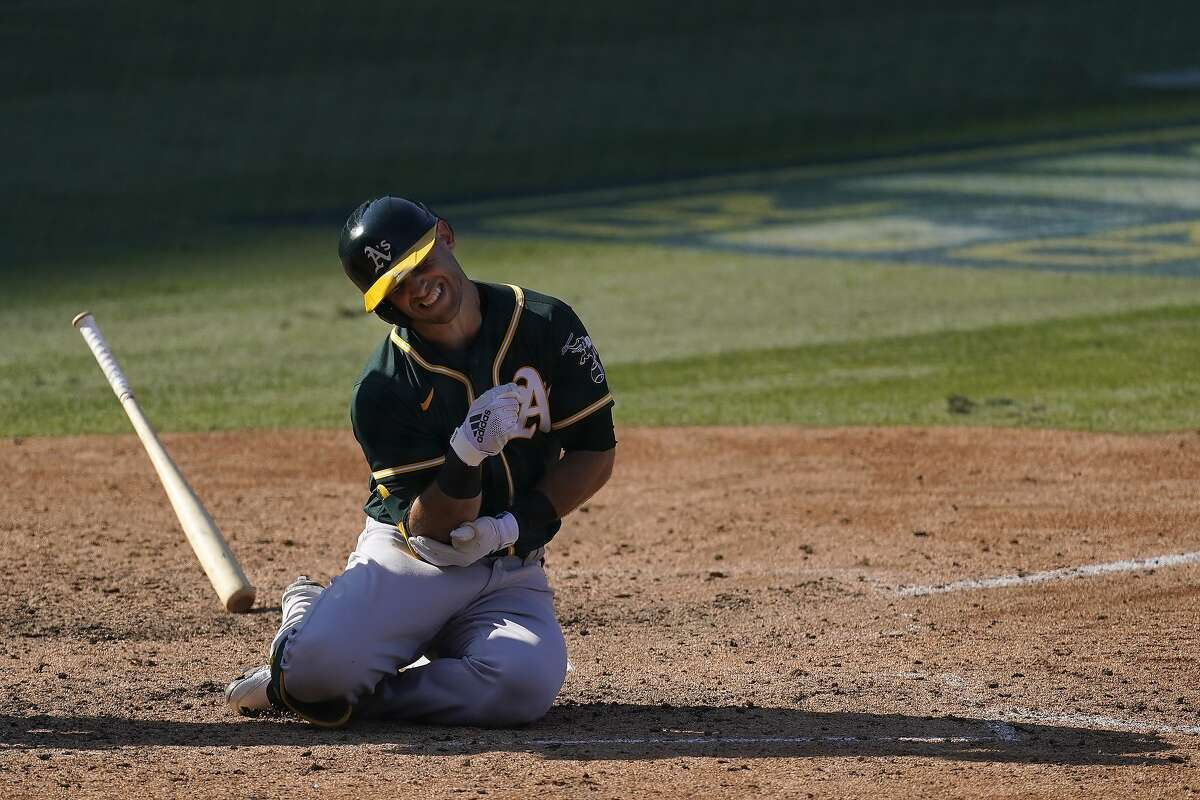 Oakland Athletics' Tommy La Stella reacts after being hit by a pitch against the Houston Astros during the eighth inning of Game 3 of a baseball American League Division Series in Los Angeles, Wednesday, Oct. 7, 2020. La Stella left the game after the play.