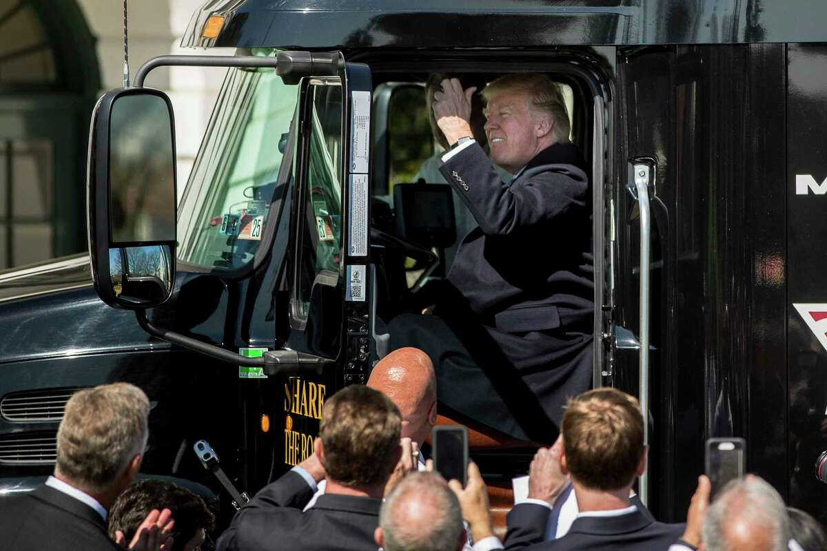 In this March 23, 2017, file photo President Donald Trump honks the horn of an 18-wheeler truck while meeting with truckers and CEOs on the South Lawn of the White House in Washington. Trump publicly acknowledged that humans bear some blame for climate change, but scientists say the president still isn't dealing with the reality of our primary role. Trump said Tuesday, Sept. 29, 2020, that humans - their tailpipe exhaust, oil and gas production, and smokestack fumes - are just one of many culprits for the weather-disrupting deterioration of Earth's atmosphere.