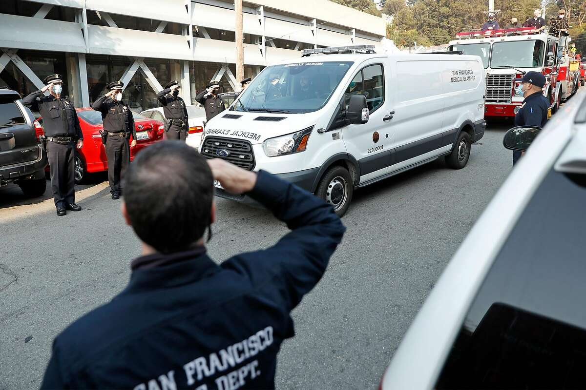 Emergency workers on 22nd Street salute as a medical examiner's van carries the body of firefighter Jason Cortez, who died in a training accident at a Mission District facility, from San Francisco General Hospital.