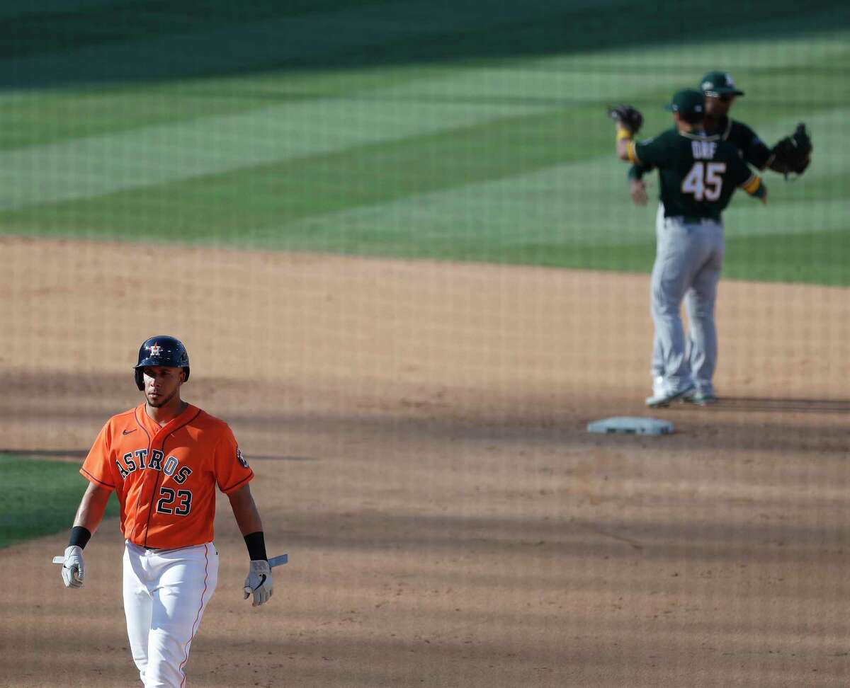Oakland Athletics celebrate in the background after Houston Astros Michael Brantley (23) flied out to left fielder Robbie Grossman for the final out of Game 3 of the American League Division Series, at Dodger Stadium, Wednesday, October 7, 2020, in Los Angeles. Astros lost the game 9-7.