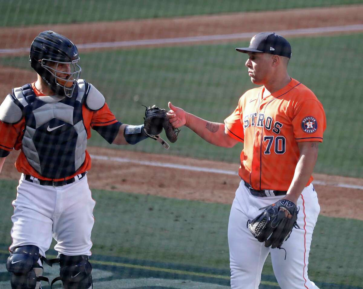 Houston Astros relief pitcher Andre Scrubb (70) high fives catcher Dustin Garneau (13) after pitching during the ninth inning of Game 3 of the American League Division Series, at Dodger Stadium, Wednesday, October 7, 2020, in Los Angeles.