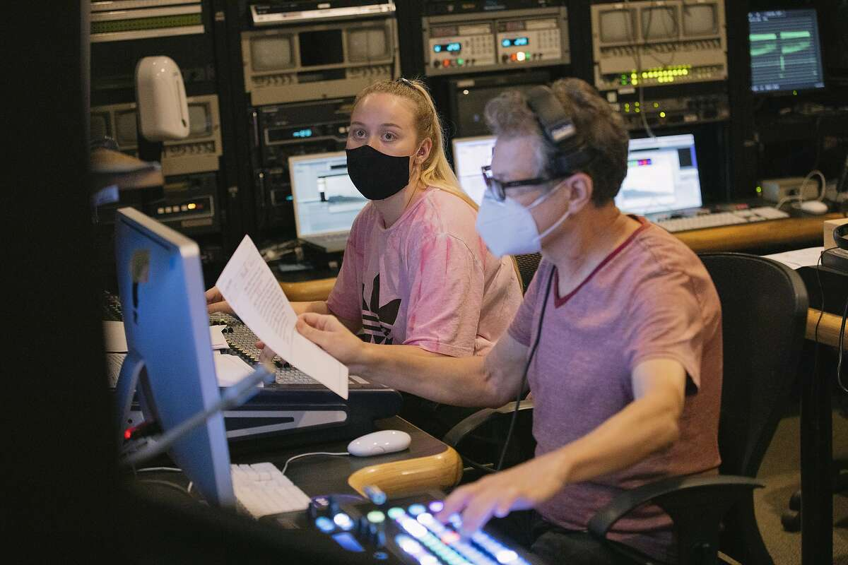 Student producer Emily Brubaker and Media Production Specialist Blasco Felipe work in the television production control room while working on an episode of Valley Views News on campus at CSU Northridge in Northridge, California September 28, 2020. Due to the pandemic, students must wear masks (except the anchors when the show is recording), keep distances when possible, and wipe down their stations for safety. All rooms have limited the amount of people allowed inside.